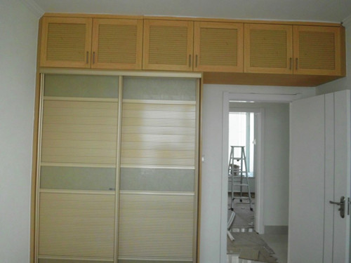 老人房衣柜选择趟门加顶柜的设计,将顶柜延伸的方式,充分利用房门